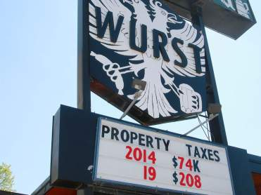 Wurst restaurant in Calgary, with sign: 'PROPERTY TAXES – 2014, $74K – 2019, $208K'